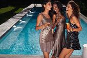 Women having drinks by swimming pool