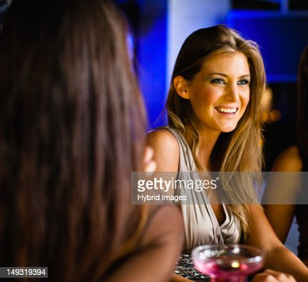 Women having drinks together at bar : Stock Photo