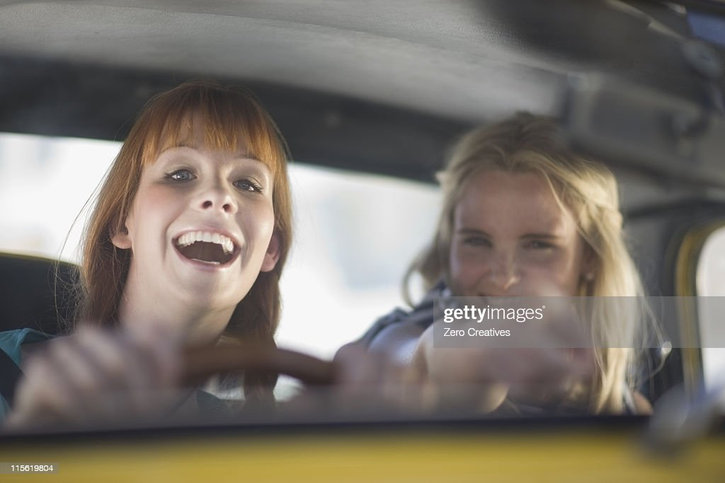 Women having fun driving a car : Stock Photo