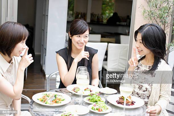 Women having meals, with finger to mouth