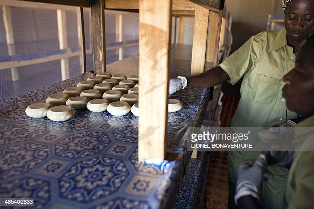 Women helped by the French cosmetics company L'Occitane programs work in the production line of their soap making factory on January 25 2014 in Leo...