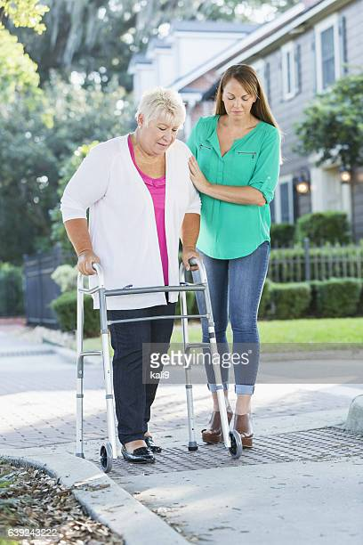 Women helping her aging mother use walker