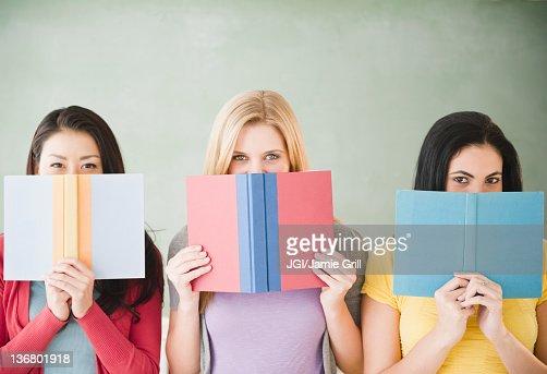 Women hiding behind books