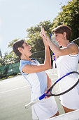 Women high-fiving after a game of doubles tennis