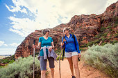 Two happy women hiking together in a red rock sandstone canyon in the deserts of Utah on an adventure vacation. Two women smiling and talking together during a fun hike