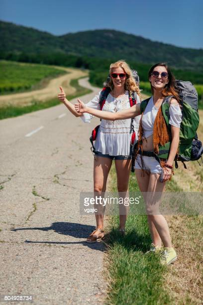 Women hitchhiking on the road trip