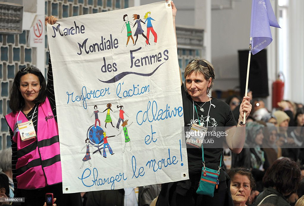 Women hold a banner at the opening of the World Social Forum (WSF) on March 26, 2013 in Tunis. More than two years after the Jasmine revolution, tens of thousands of people are expected for the WSF, dubbed the forum of 'dignity', a watchword of the Tunisian uprising that inspired revolts across the Arab world.