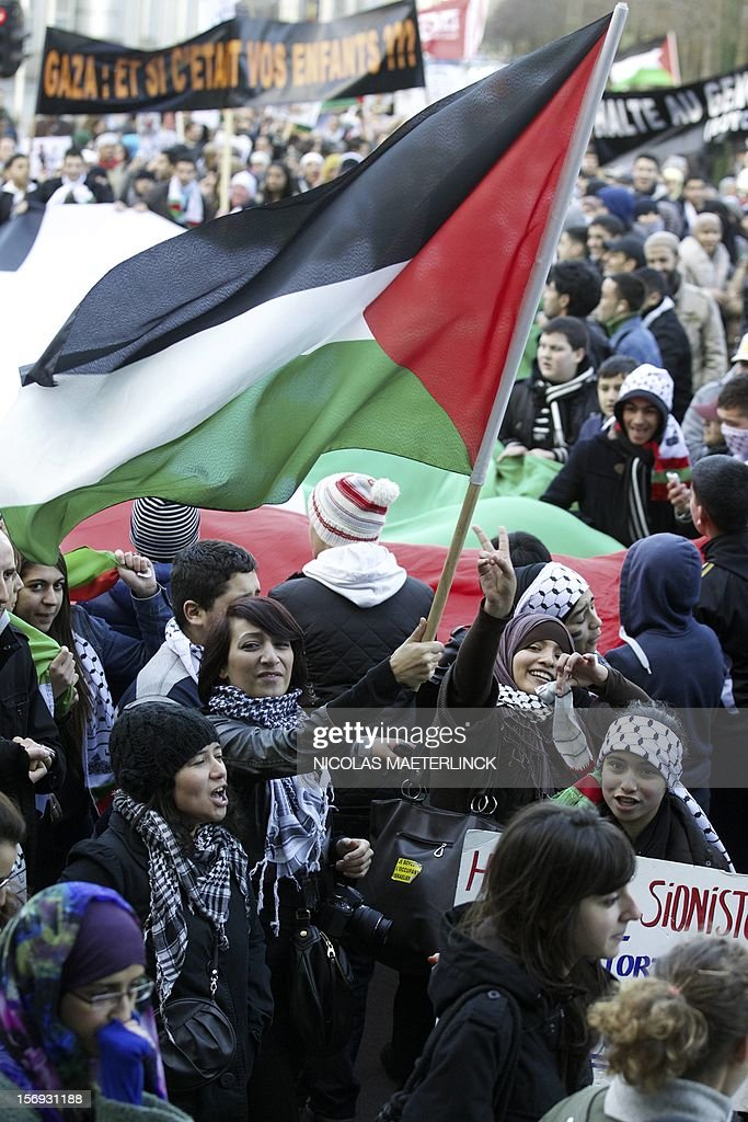 Women hold a Palestinian flag and flash victory signs as they take part in a demonstration in solidarity with Palestinians and denouncing recent Israeli bombardments on Gaza, on November 25, 2012, in Brussels.