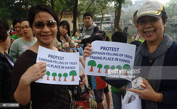 Women hold a placards as they join a rally protesting against a treefelling plan by the municipal authorities in Hanoi on March 22 2015 Vietnam...