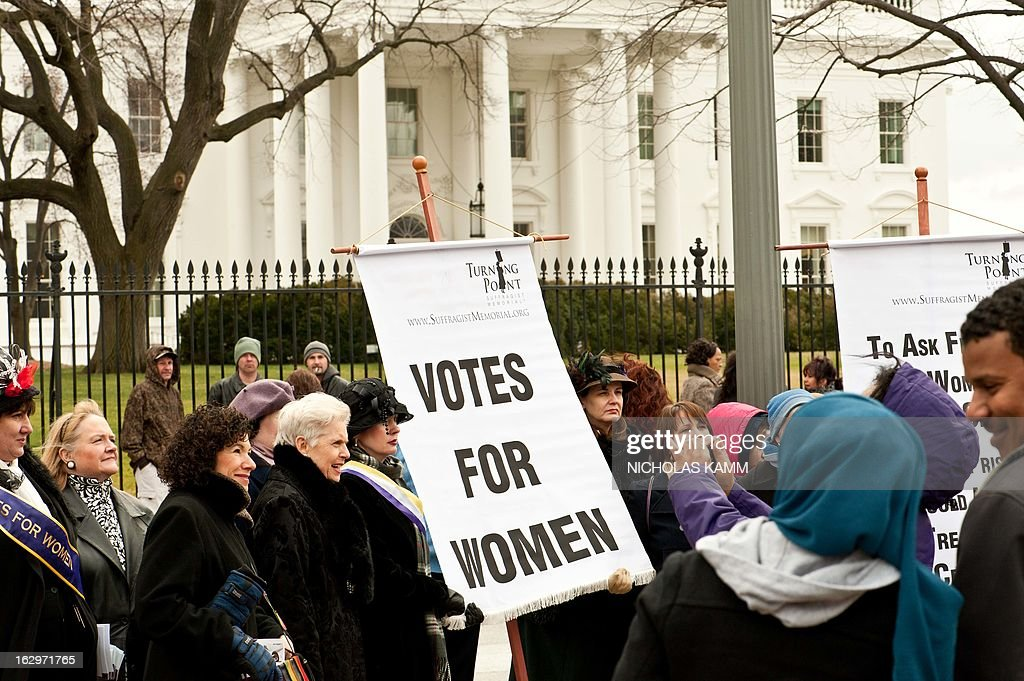 Women hold a sign in front of the White House in Washington on March 2, 2013 during an event to commemorate the 100th anniversary of the Suffrage March. On March 3, 1913, on the eve of President Woodrow Wilson's inauguration, masses of suffragists from many states filled the streets around the US Capitol, White House, and Treasury Building. In 1920, the 72-year struggle ended with the ratification of the 19th Amendment, the 'Susan B. Anthony' Amendment, granting women the vote. AFP PHOTO/Nicholas KAMM