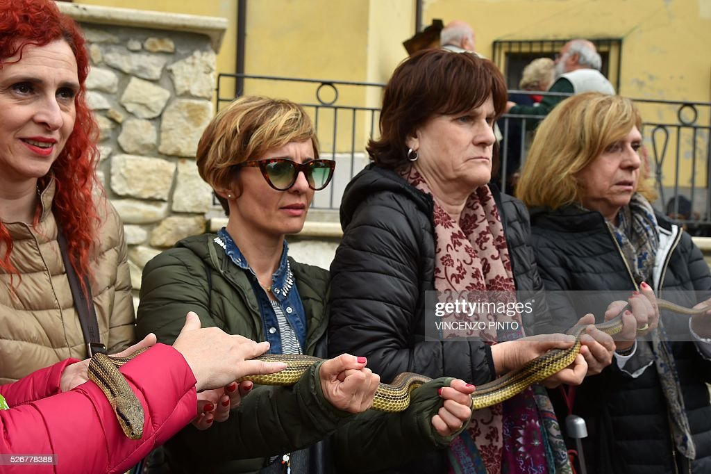Women hold a snake before the annual procession of faithful carrying a statue of Saint Domenico covered with live snakes in the streets of Cocullo, a small village in the Abruzzo region, on May 1, 2016.