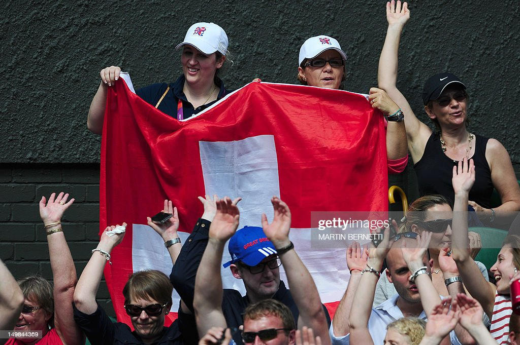 Women hold a Swiss flag as the crowd makes the Mexican wave during the men's singles gold medal match of the London 2012 Olympic Games between Great Britain's Andy Murray and Switzerland's Roger Federer, at the All England Tennis Club in Wimbledon, southwest London, on August 5, 2012.