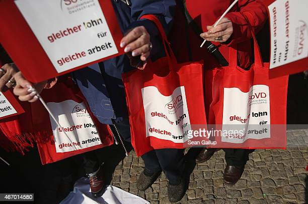 Women hold bags and signs that read 'Same pay for same work' at a rally for equal pay for women compared to men on Equal Pay Day in front of the...