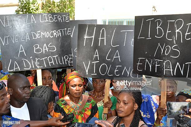 Women hold banners during a protest in Conakry on October 30 to demand the release of people arrested during Guinea's contested presidential election...