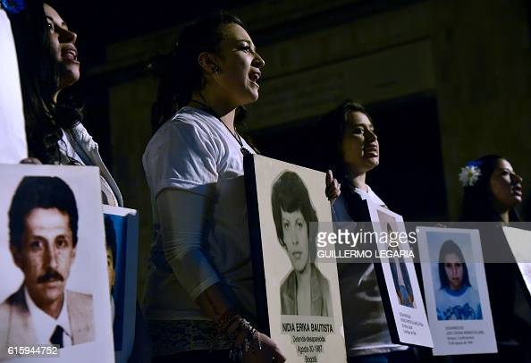 Women hold pictures of people who went missing during the armed conflict during a march for peace in Bogota on October 20 2016 Colombian President...