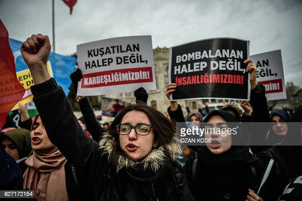 Women hold placards as they chant slogans on December 2 2016 in Istanbul during a demonstration to protest against the Syrian official regime and...