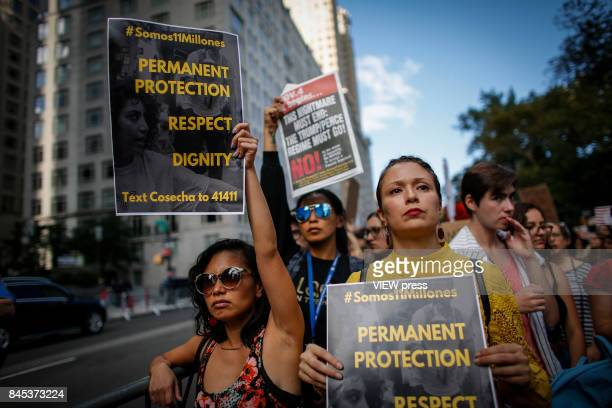 Women hold placards as they take part during a march in protest of President Trump's decision on DACA in front of a Trump Hotel on September 9 2017...