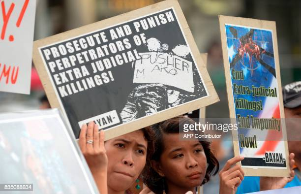 Women hold placards reading 'prosecute and punish perpetrators of extra judicial killings' 'End impunity now' during a protest against extra judicial...