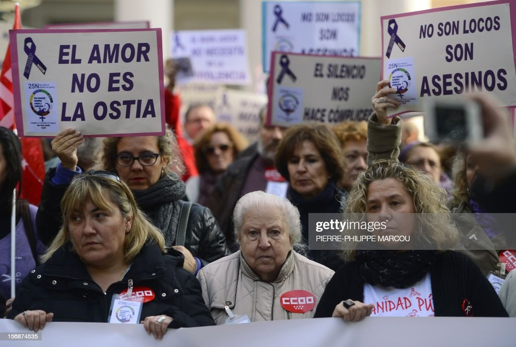 Women hold placards reading 'They are not crazy, they are murderers' (R) as they protest against domestic violence in Madrid on November 23, 2012.