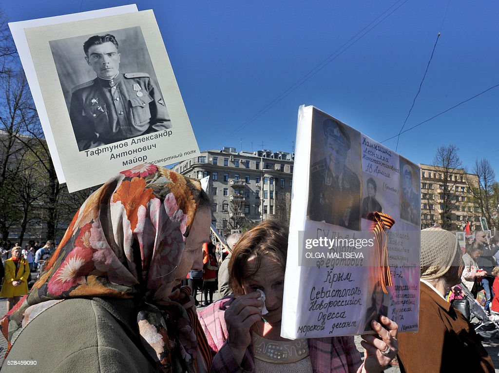 Women hold portraits of World War II soldiers as they take part in the Immortal Regiment march in central St. Petersburg on May 5, 2016. Russia will celebrate the 71st anniversary of the 1945 victory over Nazi Germany on May 9. / AFP / OLGA