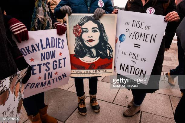 TOPSHOT Women hold posters as they take part in a march for women's rights and freedom in solidarity with the march organised in Washington on...