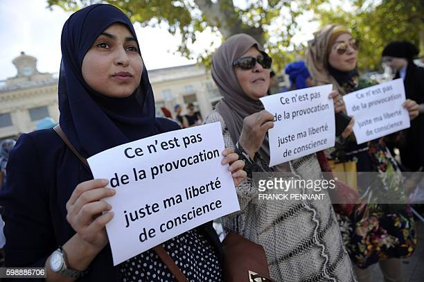 Women hold signs reading 'Is it not a provocation just my freedom of conscience' during a 'headscarf march' organized by the Collective against...