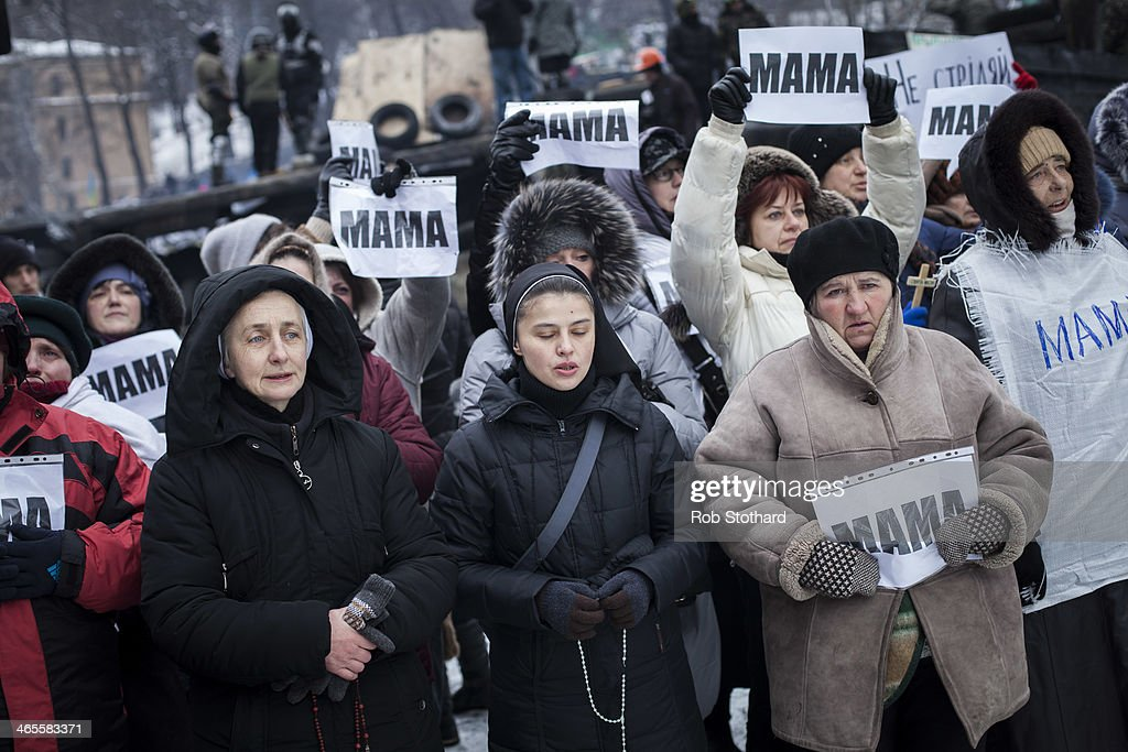 Women hold signs that reads 'mama' during a march led by Orhodox priests towards police lines, urging them not to harm protestors on Grushevskogo Street on January 28, 2014 in Kiev, Ukraine. Ukraine's parliament is holding a special session called over continuing unrest in the country and Prime Minister Mykola Azarov has offered to resign.