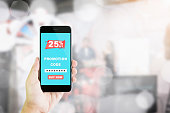 Women hold the phone to enter the code to get a discount from the store. The concept of providing marketing services on the internet for easy access to information.