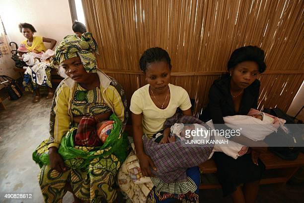 Women hold their babies as they wait for them to be vaccinated with the BCG vaccine against tuberculosis at the Noki health centre on September 10...