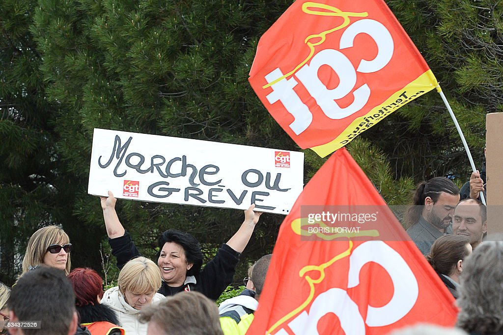 A women hold up a sign that reads 'walk or die' as members of the French union the CGT block the entrance of an industrial zone as they protest against the labour law reforms on May 26, 2016 in Vitrolles in southern France. France faced fresh strikes after nuclear power station workers voted to join gathering protests against labour law reforms that have forced the country to dip into strategic fuel reserves due to refinery blockades. Protesters are furious that the government rammed the labour market reforms through parliament without a vote, which are designed to address France's famously rigid labour market by making it easier to hire and fire workers. / AFP / BORIS