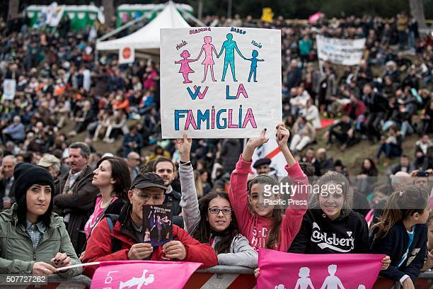 Women holding a banner with a man holding poster during demonstration in Rome 'Family Day' an event organized in defense of traditional Catholic...