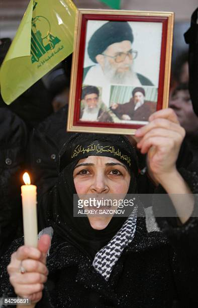 A women holding a Hezbollah flag and a portrait of Iran's supreme leader Ayatollah Ali Khamenei shouts slogans at a rally against the Israeli...