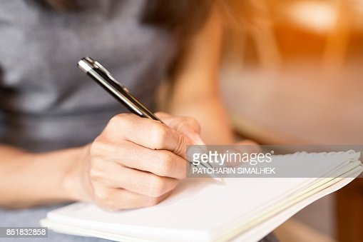 Women holding a pens writing a notebook. Recording concept : Stock Photo