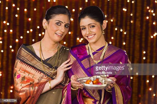 Women holding a pooja thali and smiling