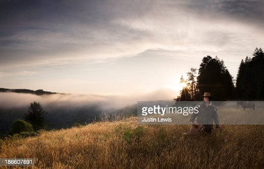 Women holding a saddle with horse on misty moutain