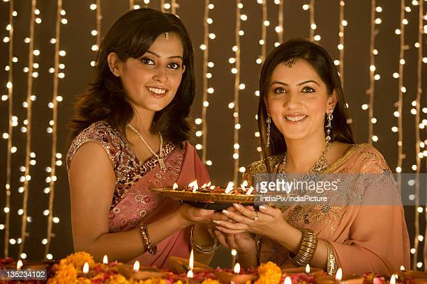 Women holding a tray of diyas
