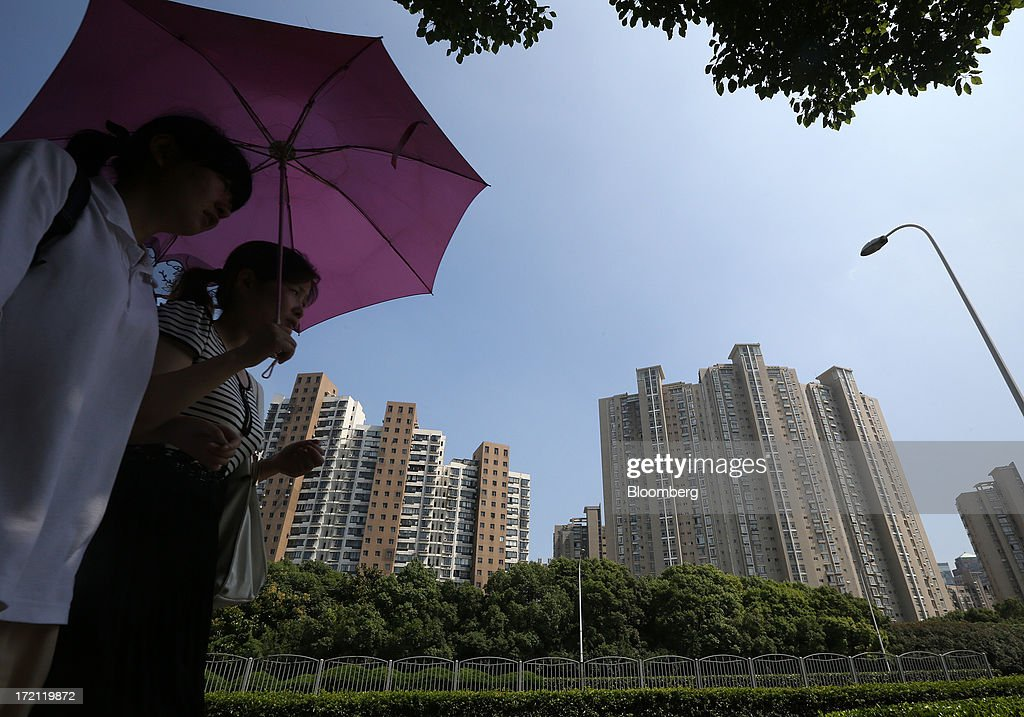 Women holding an umbrella walk past residential buildings in Shanghai, China, on Sunday, June 30, 2013. China's President Xi Jinping said officials shouldn't be judged solely on their record in boosting gross domestic product, the latest signal that policy makers are prepared to tolerate slower economic expansion. Photographer: Tomohiro Ohsumi/Bloomberg via Getty Images