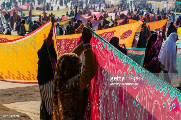 Women holding colorful fabric at festival, Allahabad, Uttar Pradesh, India