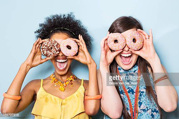 women holding doughnuts in front of eyes.