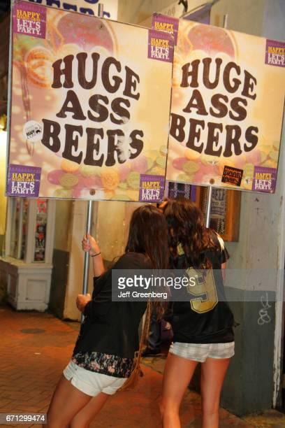 Women holding Huge Ass Beer signs