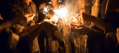 Women holding many sparklers in hands at night