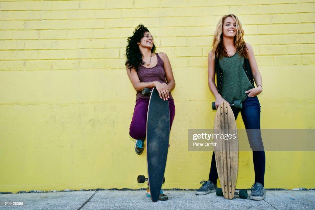 Women holding skateboards on city street