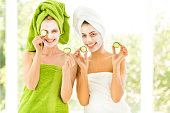 Two smiling young women with towel on head and slice of cucumber in hands.