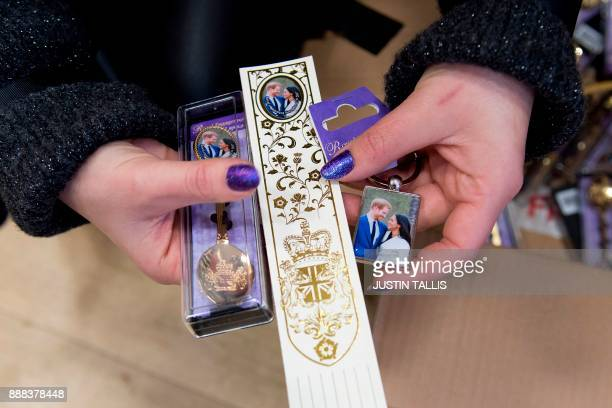 A women holds memorabilia celebrating the engagement of Britain's Prince Harry to fiancée US actress Meghan Markle in a gift shop in Windsor west of...