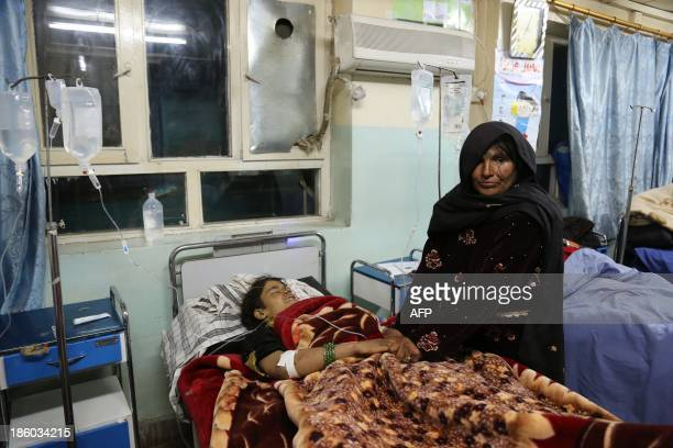 A women holds the hands of a victim of a roadside bomb at a hospital in the Andar district of the Ghazni province on October 27 2013 A roadside bomb...