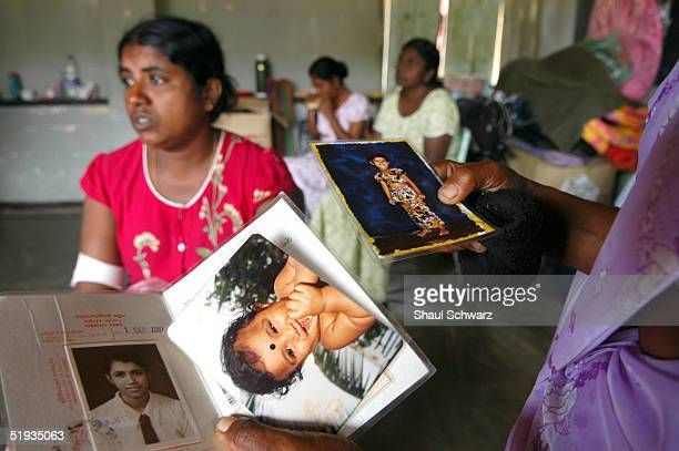 A women holds up pictures of children who have died in the tsunami disaster January 9 2005 in Matara Sri Lanka Two of the schools in town have been...