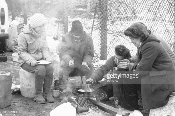 Women huddle together around camp fires in the 'Women's Peace Camp' at Greenham Common following a heavy snowfall 12th January 1987