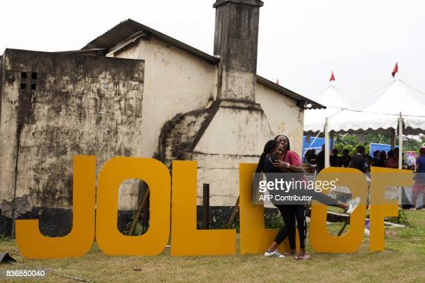 Women hug beside letters reading 'Jollof' a popular dish in Nigeria and across West Africa during the Jollof rice festival in Lagos on August 20 2017...