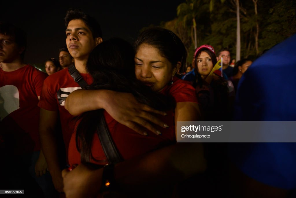 Women hug each other during the march of the supporters of President Hugo Chavez through the streets of Caracas to the military academy on March 06, 2013 in Caracas, Venezuela.