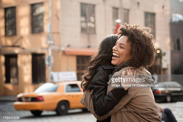 Women hugging on city street